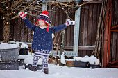 happy child girl in christmas hat on the walk in winter snowy garden throwing snow