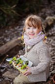 adorable happy child girl holding egg box with herbs in early spring garden