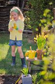 adorable blonde child girl plays little gardener and wearing rubber gloves in spring garden