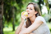 Young woman eating an apple in the park
