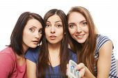 Three surprised women with TV remote control