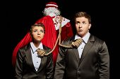 Tense business people tied to Santa Claus
