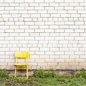 brick wall and yellow seat