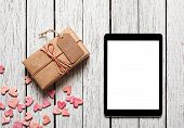 Vintage gift box with gift tag, heap of small hearts and digital tablet computer on white wooden background.