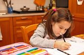 Young Girl Writes With Pencil On The Book In The Kitchen