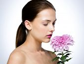 Attractive woman smelling flower over gray background