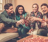 Group of multi-ethnic friends with pizza and bottles of drinks having party