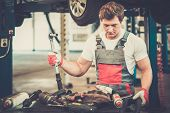 Young mechanic with tools in a car workshop