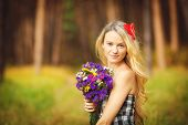A beautiful woman with a bouquet of wild flowers in the woods in the summer.