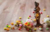 Chocolate Easter Bunny with sweet candy and flowers on the wooden table