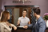 Portrait of happy female receptionist giving information to young couple.