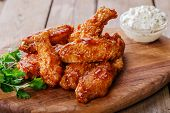 Battered chicken wings in red spicy sauce