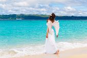 Beautiful Young Bride With Angel Wings On The Sea Coast. Tropical Sea In The Background.