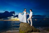 Bride And Groom On A Tropical Beach With The Sunset In The Background