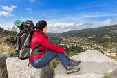 Woman Traveler With A Backpack Resting. View Of The Beautiful Landscape.