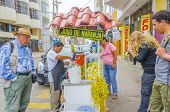 PISCO, PERU, MAY 21, 2014:  Local man prepares fresh orange juice on street stand while tourists wait for drink it