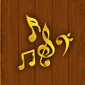 Shiny golden musical notes on wood background.