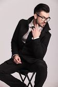 Handsome elegant business man sitting on a stool while looking down and holding two fingers to his chin.