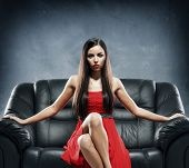 Young woman in red evening dress sitting on the black leather sofa over grey background