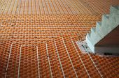 picture of floor heating  - Orange Underfloor heating tube in a construction site with stairs - JPG