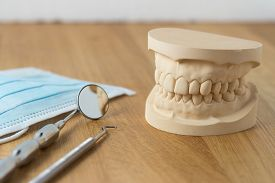 picture of false teeth  - Dental mold showing the teeth of the upper and lower jaw with dental tools and a face mask on a wooden table in a dental care and examination concept - JPG