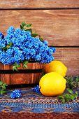 foto of blue-bell  - Blue bell flowers with lemon on wooden background - JPG