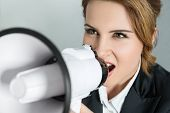 stock photo of shout  - Closeup portrait of young business woman shouting with a megaphone - JPG