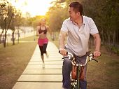 picture of exercise bike  - young asian couple running riding bike outdoors in park at sunset - JPG