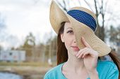 picture of windy  - Freckled woman covering one eye by hat in windy weather - JPG