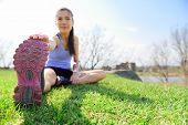 picture of hamstring  - Fit fitness woman doing stretching exercises outdoors on grass - JPG
