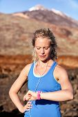 stock photo of heart sounds  - Runner looking at heart rate monitor sports smart watch after running with earphones listening to music - JPG