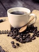 foto of sackcloth  - Cup of coffee and coffee beans on sackcloth and old wooden table - JPG