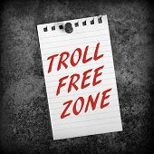 stock photo of troll  - Black and white image of lined paper pinned to a grunge background with the phrase Troll Free Zone in red text - JPG