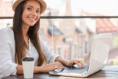 foto of funky  - Beautiful young woman in funky hat working on laptop and smiling while sitting outdoors - JPG