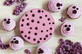 pic of berries  - Cupcakes with traditional berry souffle dessert decorated with fresh berries and lilac on white kitchen table background - JPG