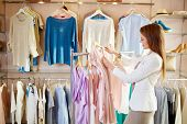 image of blouse  - Elegant girl choosing blouse from new collection of clothes in boutique - JPG