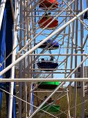 stock photo of amusement park rides  - ride a Ferris wheel at an amusement park against the blue sky - JPG