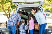 picture of road trip  - Happy family getting ready for road trip on a sunny day - JPG