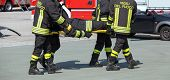 stock photo of stretcher  - Four brave Firefighters carry a fellow firefighter with the medical stretcher - JPG