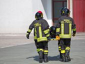 foto of stretcher  - Four brave Firefighters carry a fellow firefighter with the medical stretcher - JPG