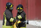 image of fire brigade  - two firemen in action with foam to put out the fire - JPG