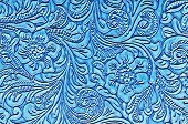 picture of leather tool  - A close up photo of a unique floral pattern on blue leather with nice shapes of flowers and leaves - JPG