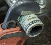 stock photo of pipe wrench  - Photograph of pipe wrench gripping twenty dollar bill - JPG