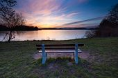 Постер, плакат: Colorful Sunset Over Lake Shore With Bench