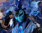 pic of carnivale  - a party goer stands in a crown in front of st markos church in st marks square venice italy to celebrate carnivale the original mardi gras - JPG