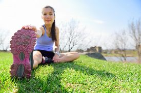 stock photo of crossed legs  - Fit fitness woman doing stretching exercises outdoors on grass - JPG