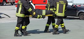 pic of firefighter  - Four brave Firefighters carry a fellow firefighter with the medical stretcher - JPG