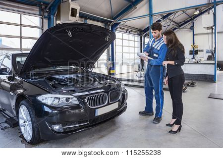 Car mechanic and customer stand next to the serviced car and looking through the checklist. The car