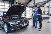 Car mechanic and customer stand next to the serviced car and looking through the checklist. The car  poster