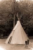 stock photo of teepee  - A traditional Indian teepee photographed in a faux antique faded sepia style simulating an early 20th century photograph - JPG